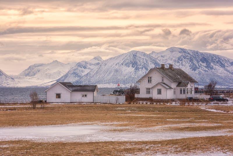 Schöne norwegische Wintersonnenunterganglandschaft, weißes Haus auf der Seeküste auf dem schneebedeckten felsige Gebirgshintergru stockfotografie