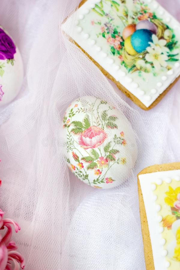 Schöne Ostereier verziert mit Papierservietten und Blumen auf weißem Tulle-Hintergrund lizenzfreie stockfotografie