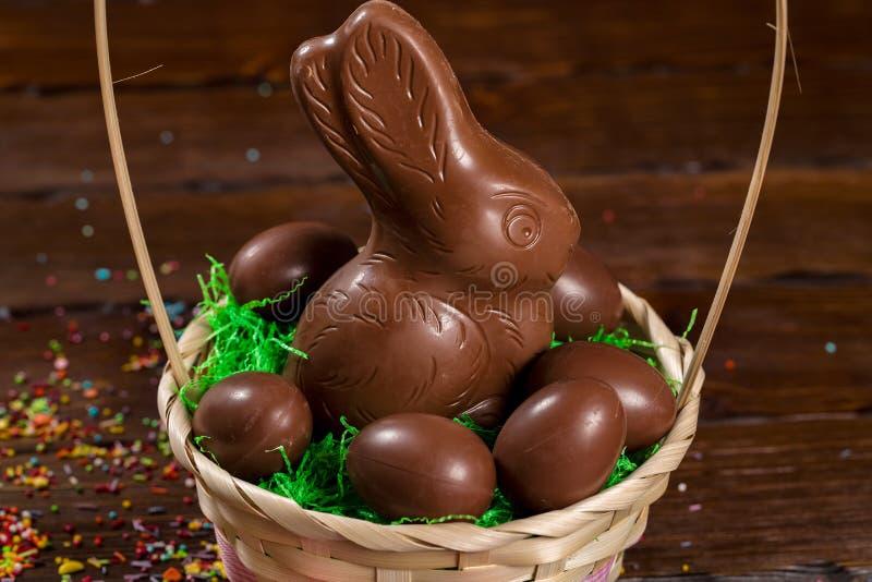 Schöne Ostern-Zusammensetzung mit Schokoladenhäschen und Eier in einem Weidenkorb mit einem Bogen, farbiges Pulver für Kuchen lizenzfreies stockfoto