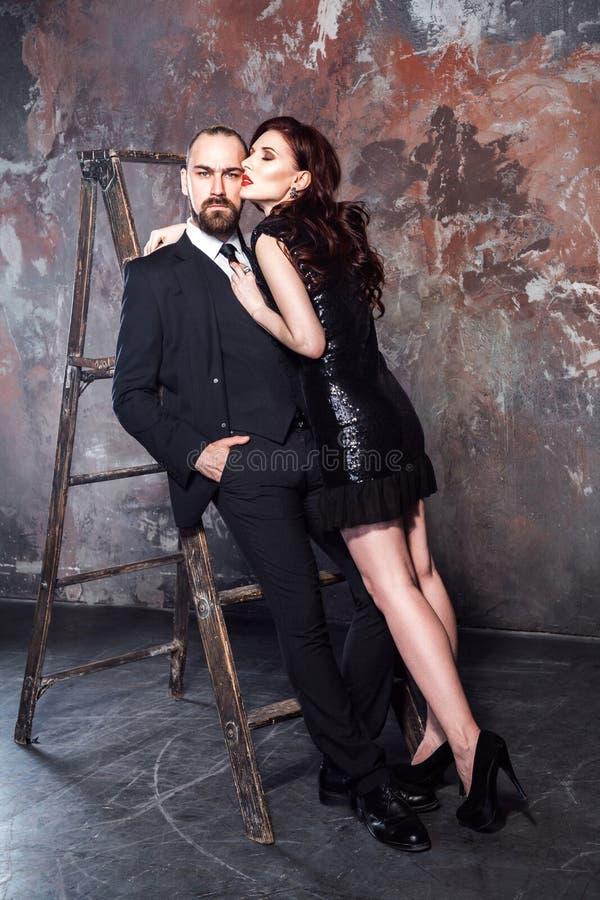 Schöne Paare, bärtiger Mann und rote Hauptfrau, die Mann umarmt Atelieraufnahme, auf sch?biger Wand lizenzfreie stockbilder