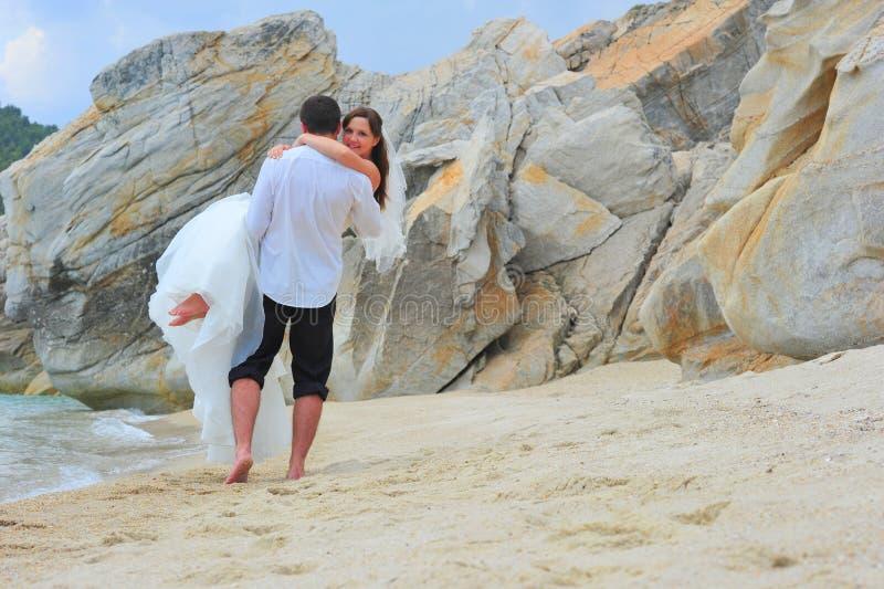 Schöne Paare der Jungvermählten am Strand lizenzfreie stockbilder