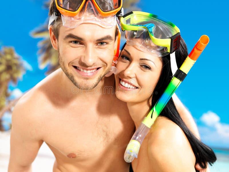 Schöne Paare des Spaßes am tropischen Strand mit Schwimmenmaske lizenzfreies stockfoto