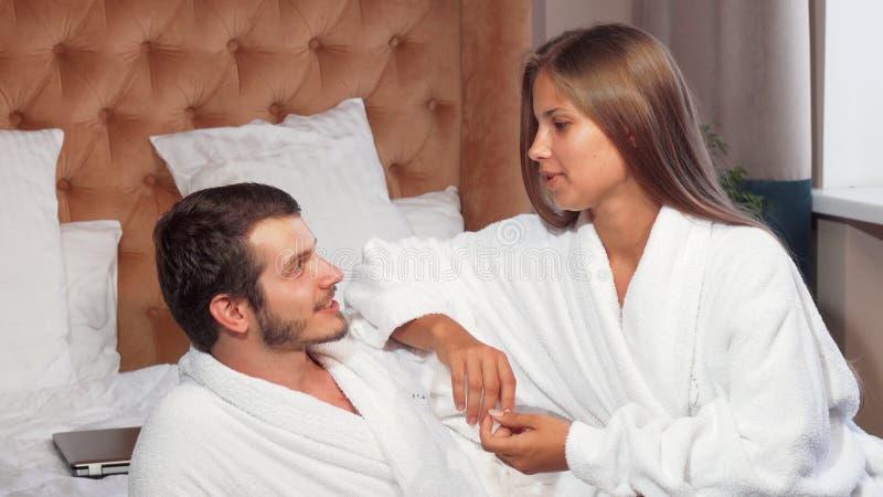 Schöne Paare, die sich zusammen im Bett, tragende Bademäntel entspannen stockbild