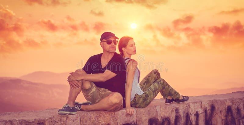 Schöne Paare, die Sonnenuntergang genießen lizenzfreies stockfoto