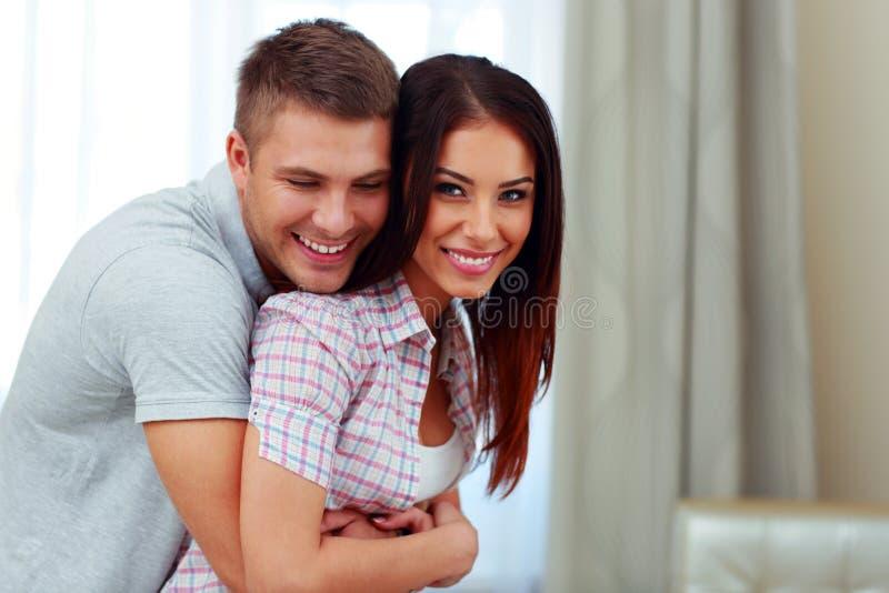 Schöne Paare, die zu Hause umarmen lizenzfreie stockfotos