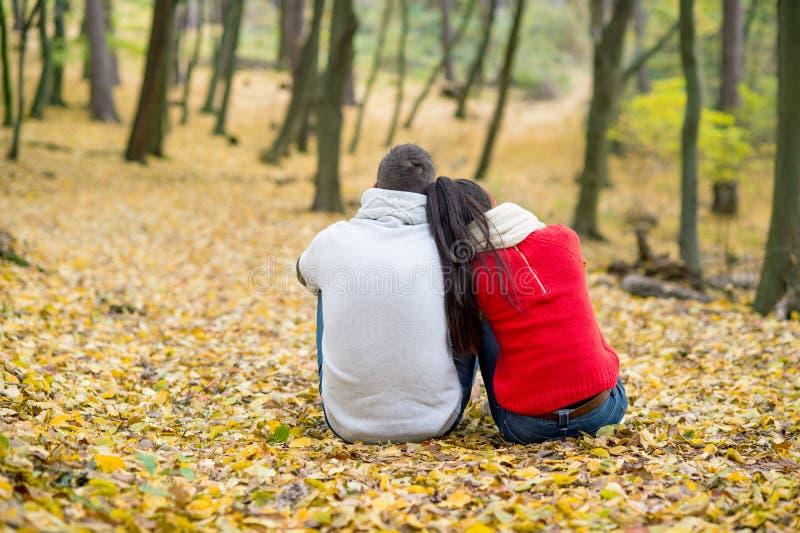 Schöne Paare im Herbst parken das sitzen aus den Grund lizenzfreie stockfotos