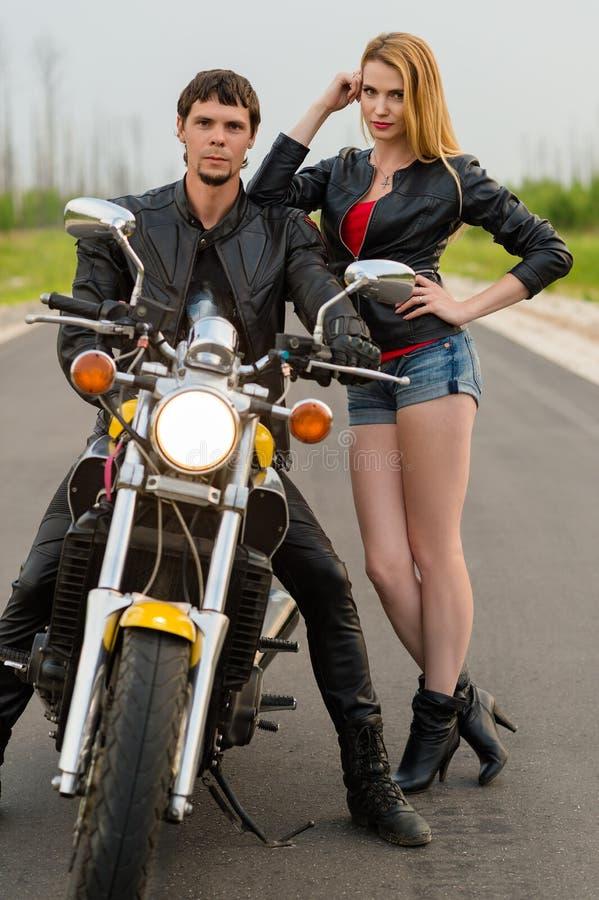 Schöne Paarradfahrermotorradfahrer auf der Straße stockfoto