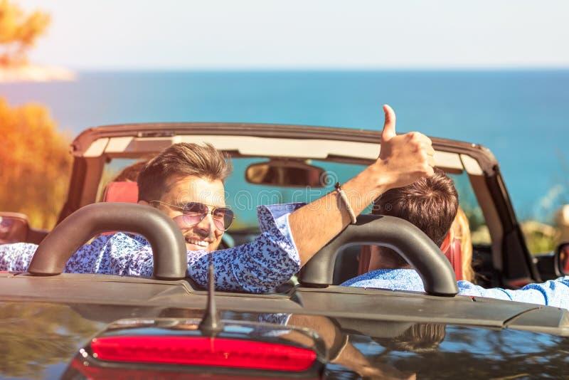 Schöne Parteifreundmädchen, die in ein Auto auf dem Strand glücklich tanzen stockbilder