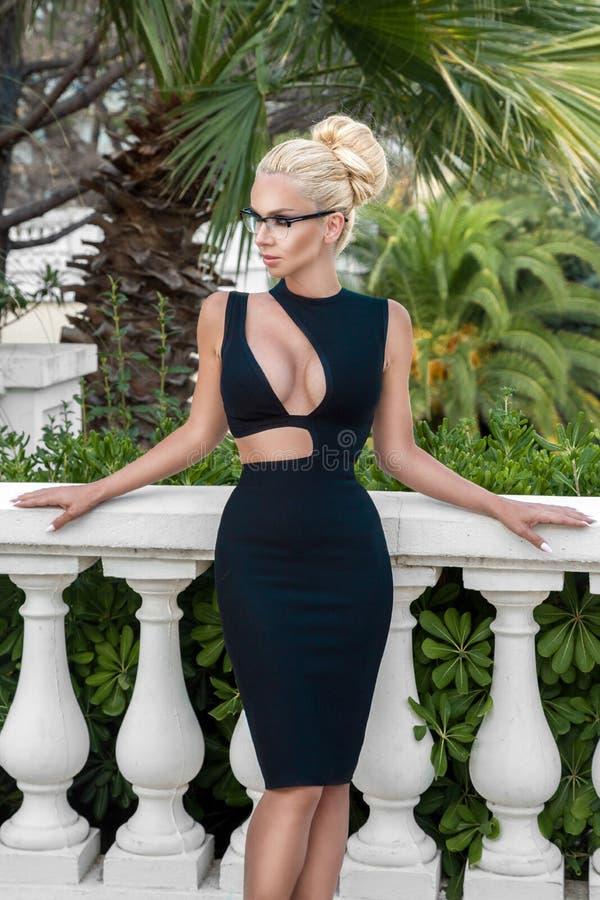 Schöne phänomenale erstaunliche elegante sexy blonde vorbildliche Luxusfrau, die ein elegantes schwarzes Kleid und hohe Absätze t lizenzfreies stockfoto
