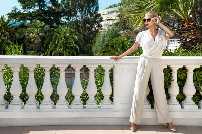 Schöne phänomenale erstaunliche elegante sexy blonde vorbildliche Luxusfrau, die einen eleganten Anzug und hohe Absätze und Sonne lizenzfreie stockbilder