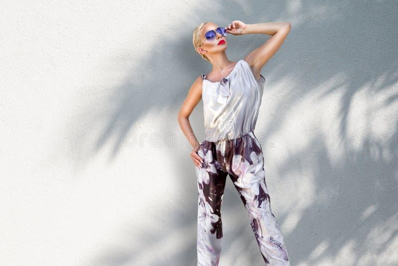 Schöne phänomenale erstaunliche elegante sexy blonde vorbildliche Luxusfrau, die einen eleganten Anzug und hohe Absätze und Sonne stockfotografie