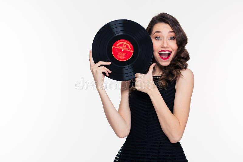 Schöne positive Frau, die Vinylaufzeichnung hält und sich Daumen zeigt stockfotos