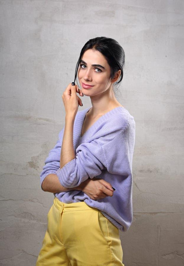 Schöne positive junge zufällige Frau, die in der violetten Strickjacke und in den gelben Hosen auf grauem Studiohintergrund aufwi stockfotografie