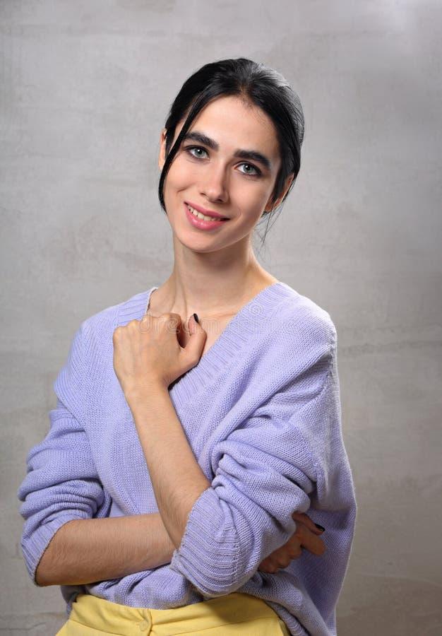 Schöne positive junge zufällige Frau, die in der violetten Strickjacke und in den gelben Hosen auf grauem Studiohintergrund aufwi lizenzfreie stockbilder