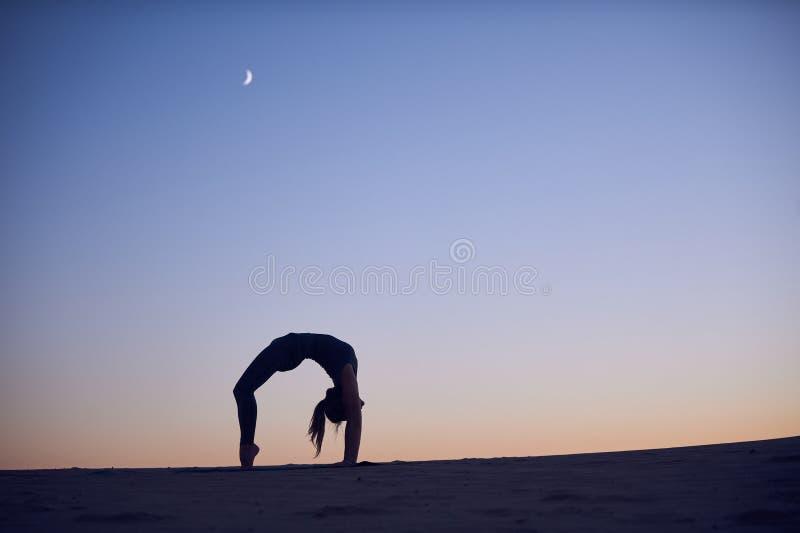 Schöne Praxis der jungen Frau rückbiegt Yoga asana Urdhva Dhanurasana - aufwärts gegenüberstellende Bogenhaltung in der Wüste nac lizenzfreie stockfotografie
