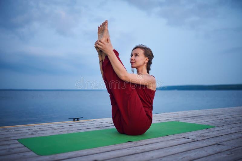 Schöne Praxisyoga asana Paripurna Navasana der jungen Frau Haltung auf der hölzernen Plattform nahe dem See stockfoto