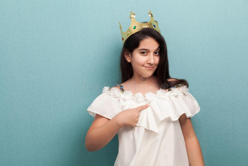 Sch?ne Prinzessin der jungen Arroganz tragen im wei?en Kleid und goldenen im Diadem und stehen und zeigen Finger auf und betracht stockfotos