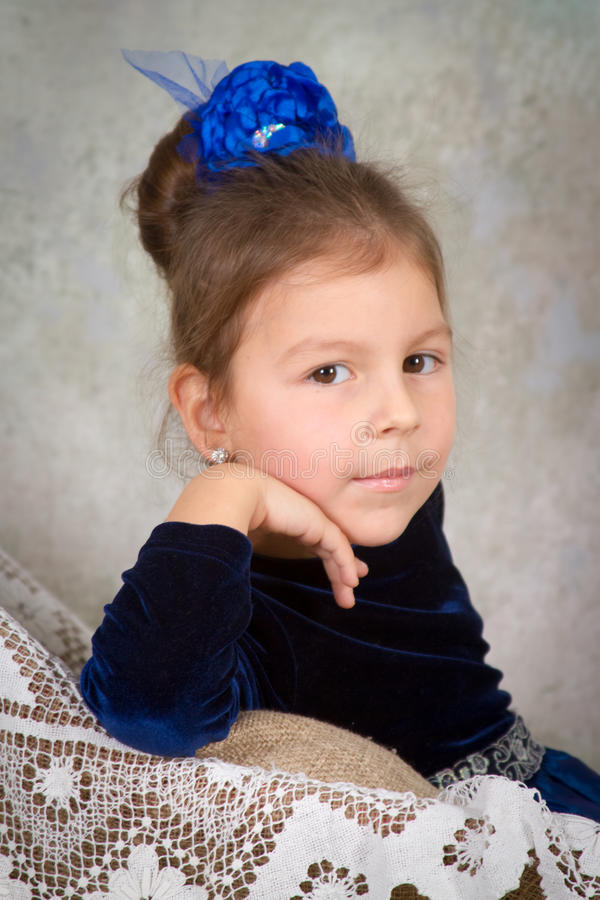 Schöne Prinzessin des kleinen Mädchens im blauen Kleid, das auf weißem Stuhl sitzt stockfoto