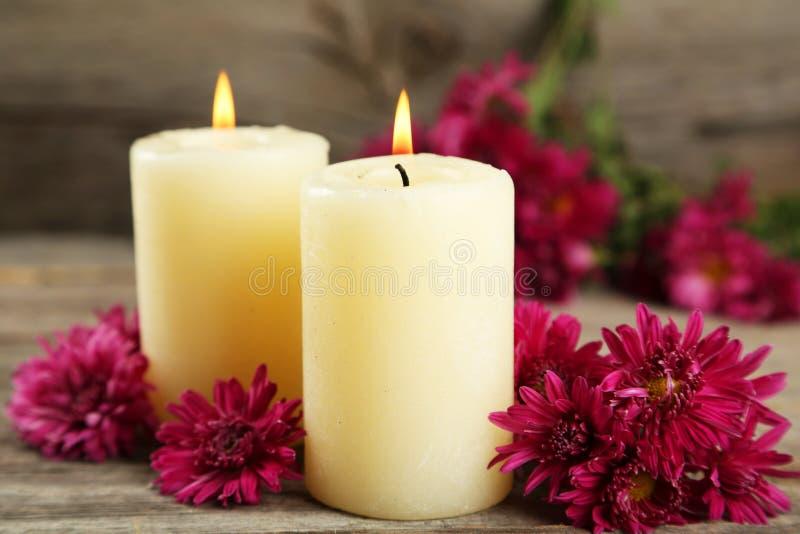 Schöne purpurrote Chrysanthemen mit Kerzen auf grauem hölzernem Hintergrund lizenzfreie stockbilder