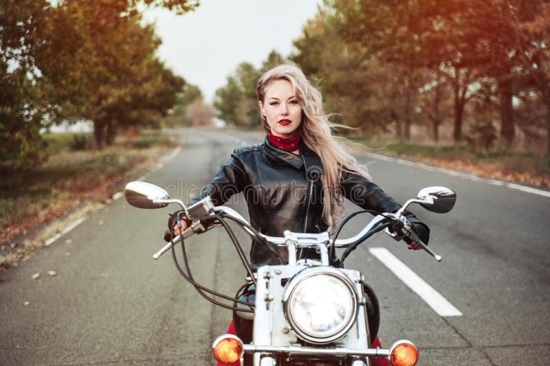 Schöne Radfahrerfrau im Freien mit Motorrad stockbild