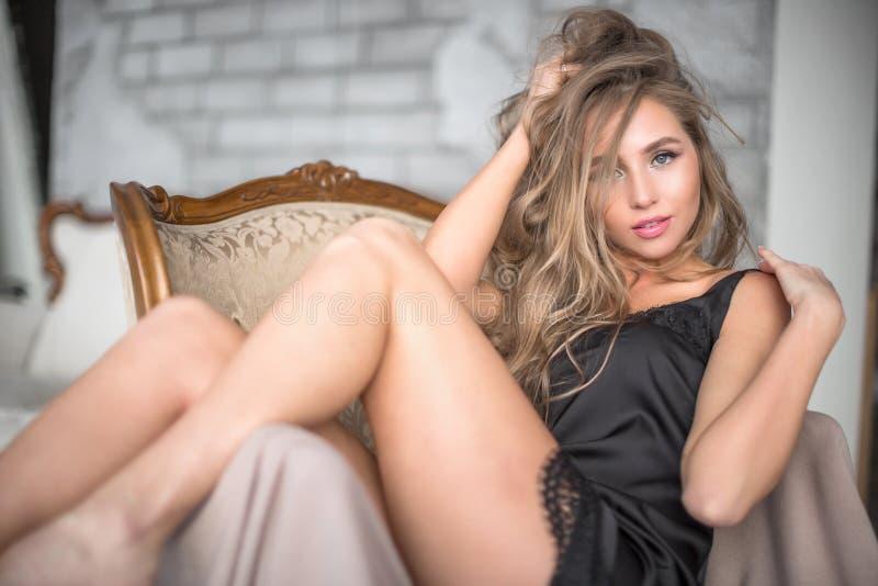 Schöne recht blonde Frau mit dem langen gewellten Haar im schwarzen kurzen Kleid, das auf Weinleselehnsessel im Schlafzimmer aufw stockfotos