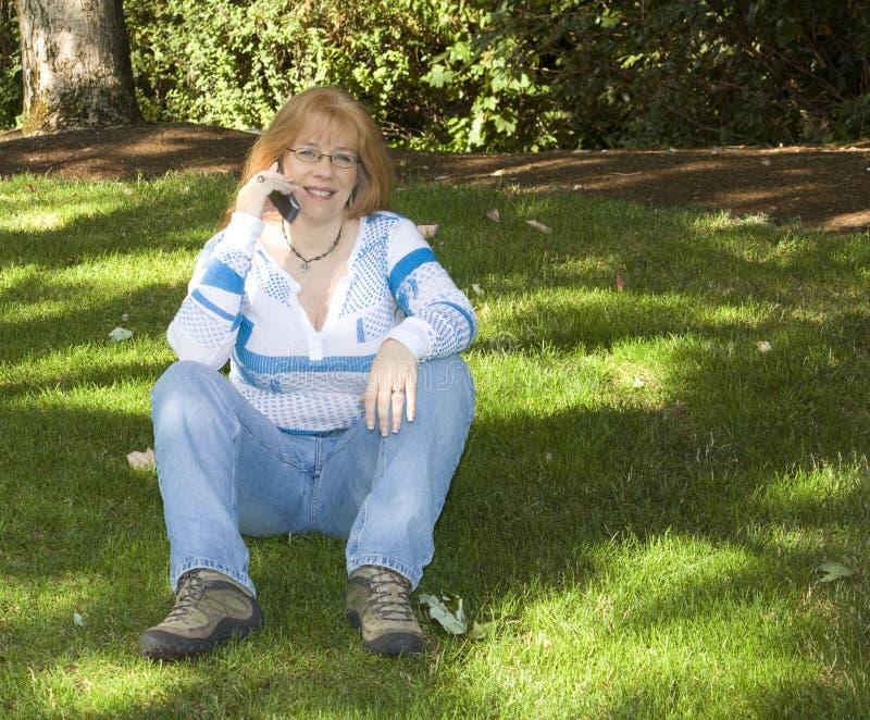Schöne Redhead-Frau, die auf Handy spricht stockbilder