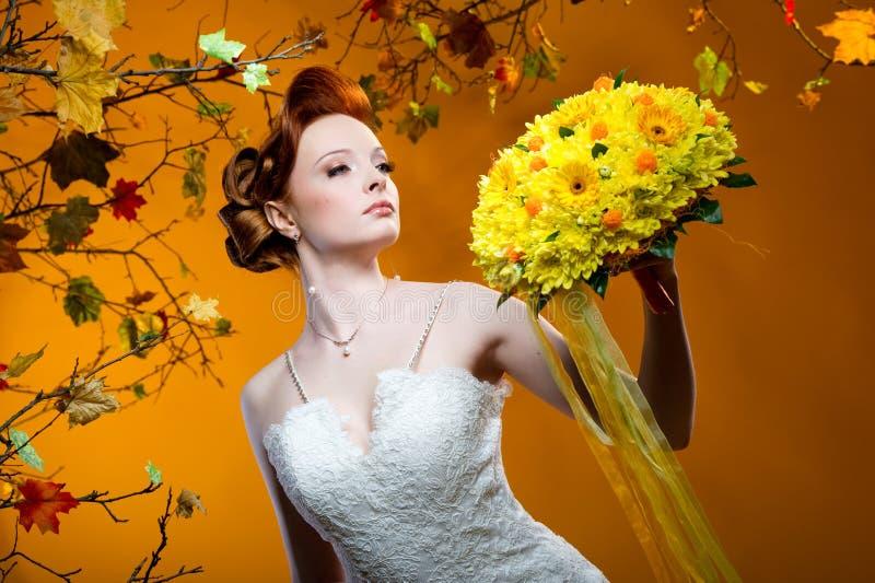 Schöne Redheadbraut mit einem Blumenstrauß der Blumen stockbilder