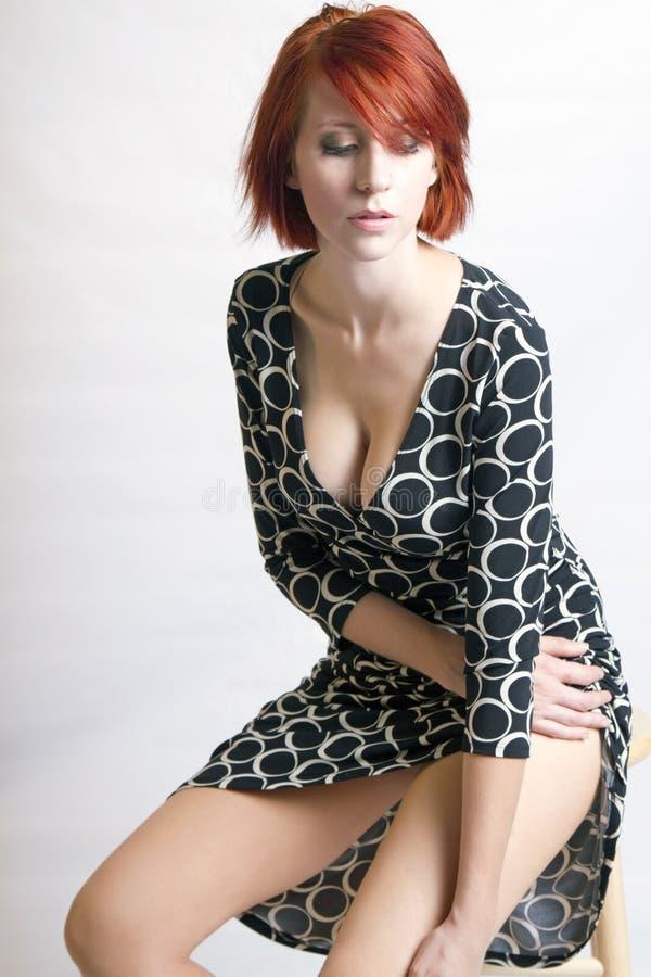 Schöne Redheadfrau auf einem Schemel stockfotografie