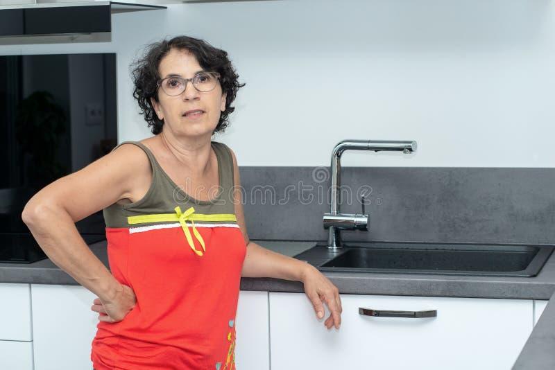 Schöne reife Frau in der Küche lizenzfreie stockfotografie