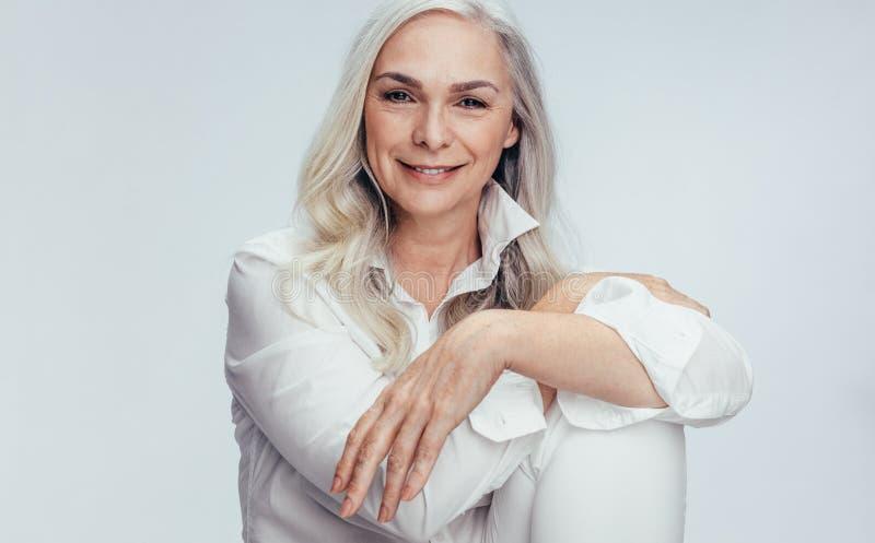 Schöne reife Frau, die über weißem Hintergrund sitzt lizenzfreie stockfotos