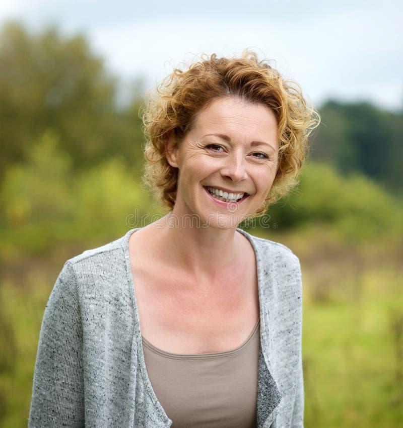 Schöne reife Frau, die im Park lächelt lizenzfreie stockfotografie