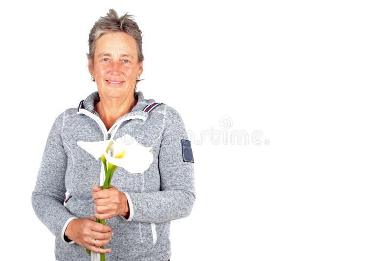 Schöne reife Frau mit blühenden Cala-Blumen lizenzfreie stockbilder