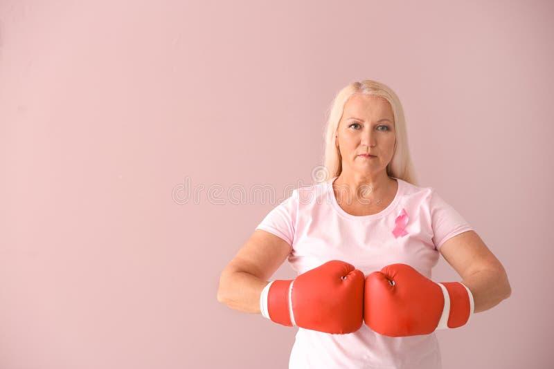 Schöne reife Frau mit rosa Band und Boxhandschuhe auf Farbhintergrund Scheren, die rosafarbenen B?stenhalter schneiden stockfotos