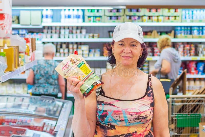 Schöne reife Frauen, die im Supermarkt einen Satz Mayonnaise zeigen lizenzfreie stockfotos