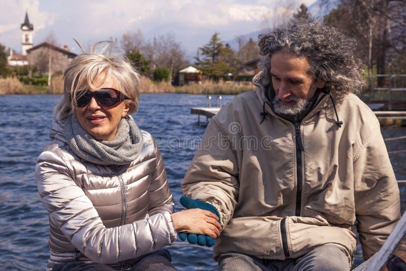 Schöne reife Paare, die den Spaß sitzt auf einem Boot haben lizenzfreie stockfotografie