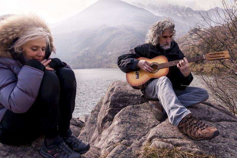Schöne reife Paare, die eine Gitarre sitzt auf dem See spielen stockbild