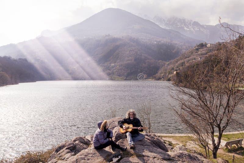 Schöne reife Paare, die eine Gitarre sitzt auf dem See spielen lizenzfreie stockbilder
