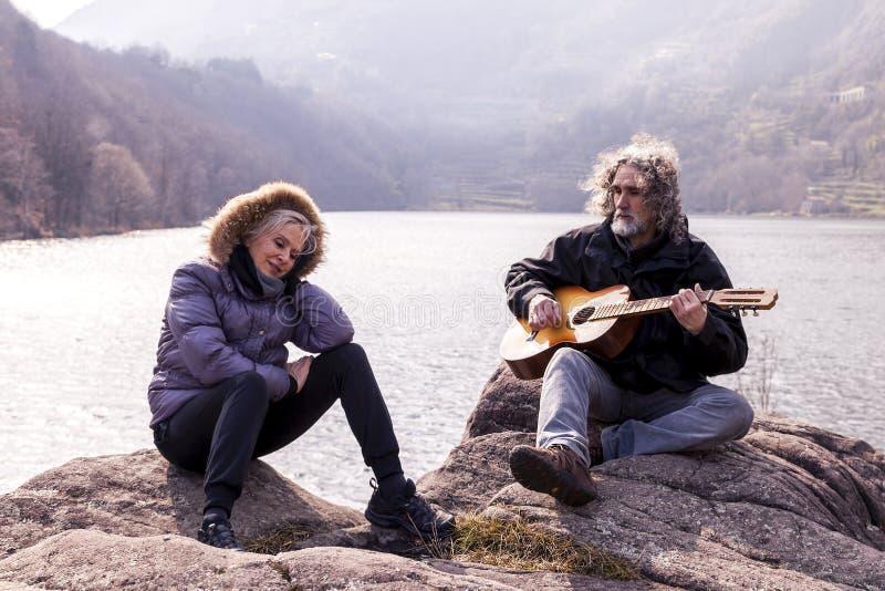 Schöne reife Paare, die eine Gitarre sitzt auf dem See spielen stockfotos
