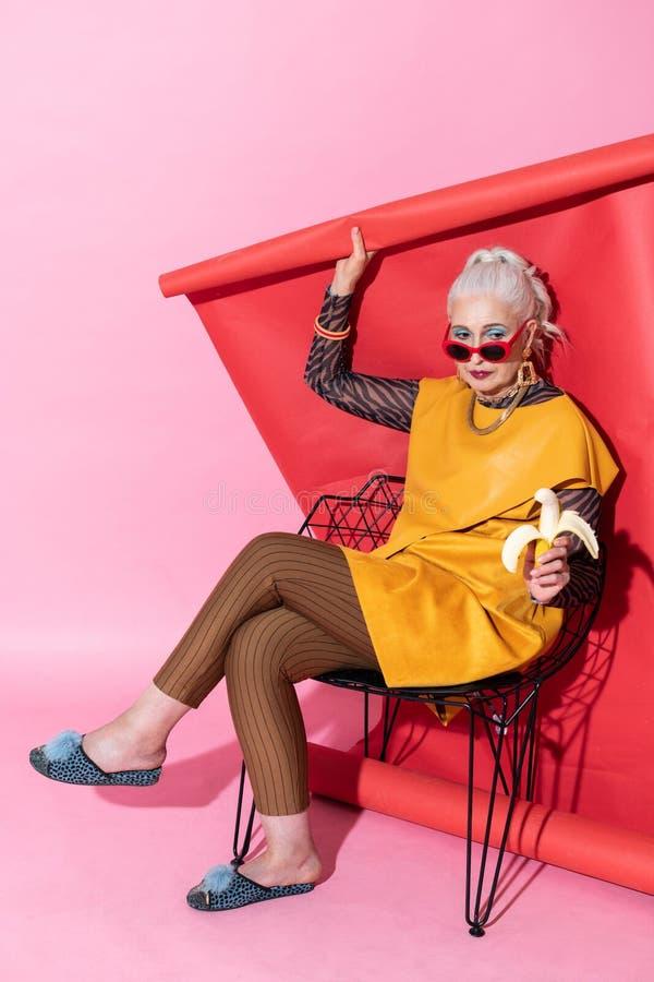 Schöne reife weibliche Person, die Banane für das Mittagessen isst stockfotografie