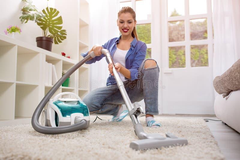 Schöne Reinigung der jungen Frau mit Staubsauger stockfoto