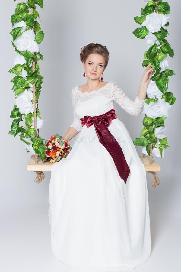 Schöne reizende Braut sitzt auf einem Schwingen mit einem schönen Blumenstrauß von bunten Blumen in einem weißen Kleid mit Abendf lizenzfreie stockbilder