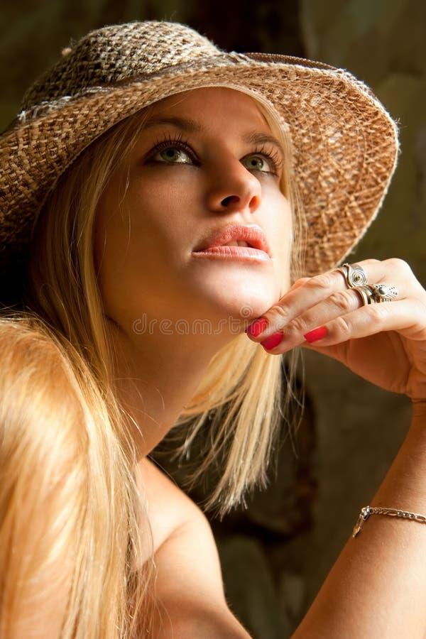 Schöne reizende Frau mit der Strohhutaufstellung lizenzfreie stockbilder