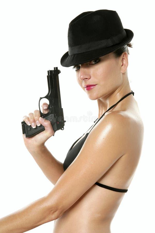 Schöne reizvolle Bikinifrau mit schwarzer Gewehr stockbilder