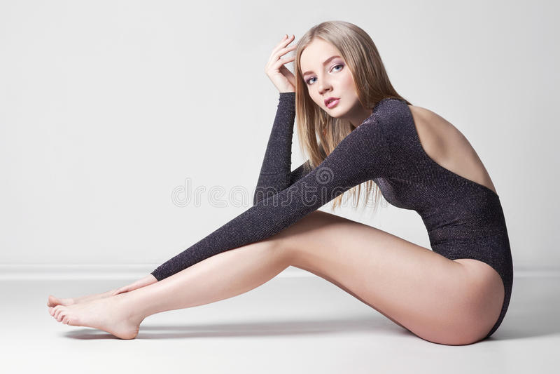 Schöne reizvolle blonde Frau Mädchen mit dem perfekten Körper, der auf Boden sitzt Schönes langes Haar und Beine, glatte saubere  stockbild