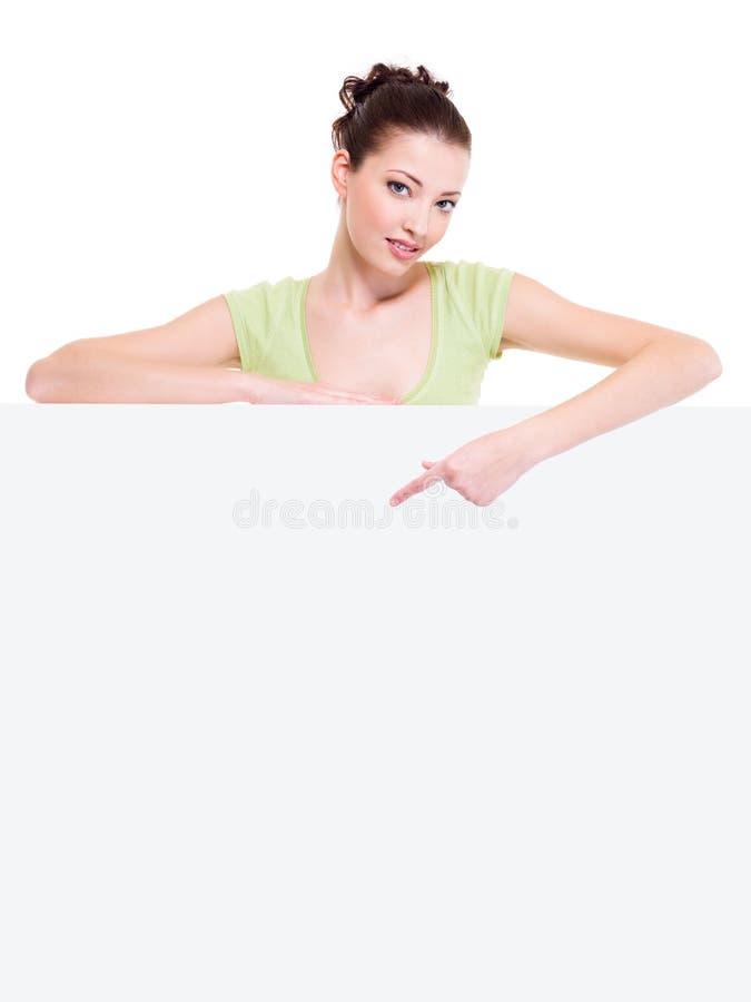 Schöne reizvolle Frau zeigt auf ein Weißbuch stockbild