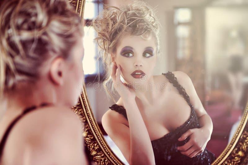 Schöne reizvolle junge Frau nahe einem Spiegel stockfotografie