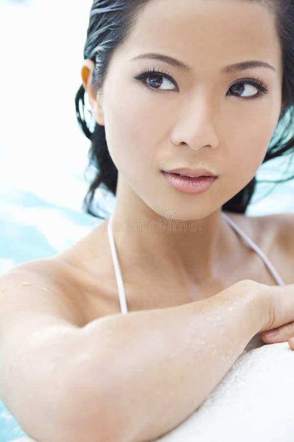 Schöne reizvolle orientalische Frau im Swimmingpool stockfoto
