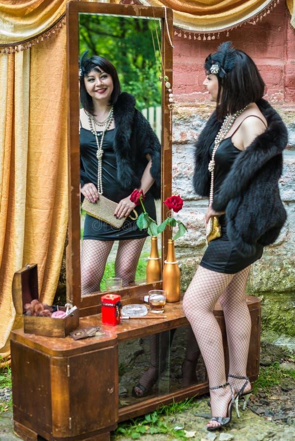 Schöne Retro- Frau schaut im Spiegel stockbild
