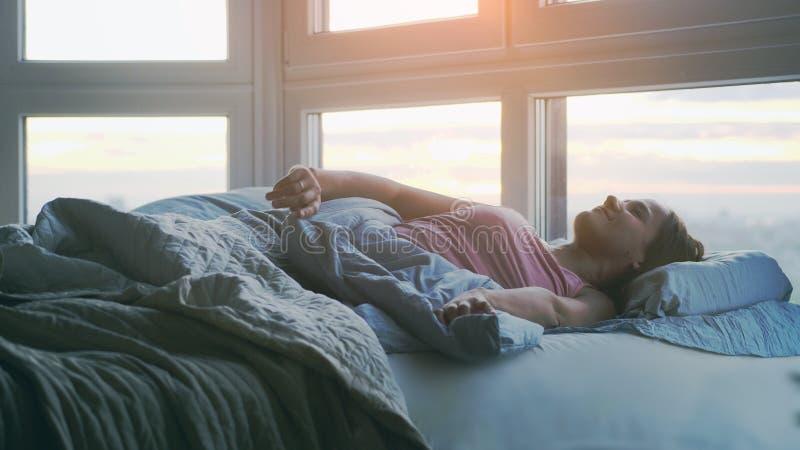 Schöne romantische brunette Frau wacht das Lügen auf dem Bett in ihrer versteckenden Decke des Raumes auf stockfotografie