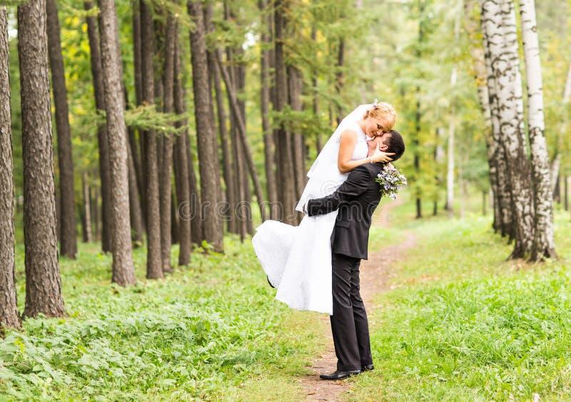 Schöne romantische Hochzeits-Paare, die draußen küssen und umfassen stockbild